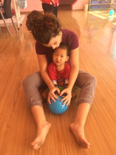 Jo sitting on the floor holding a child and blue ball